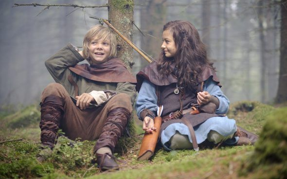 Dziewczynka i chłopiec siedzący pod drzewem.