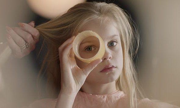 Dziewczynka patrząca przez taśmę klejącą